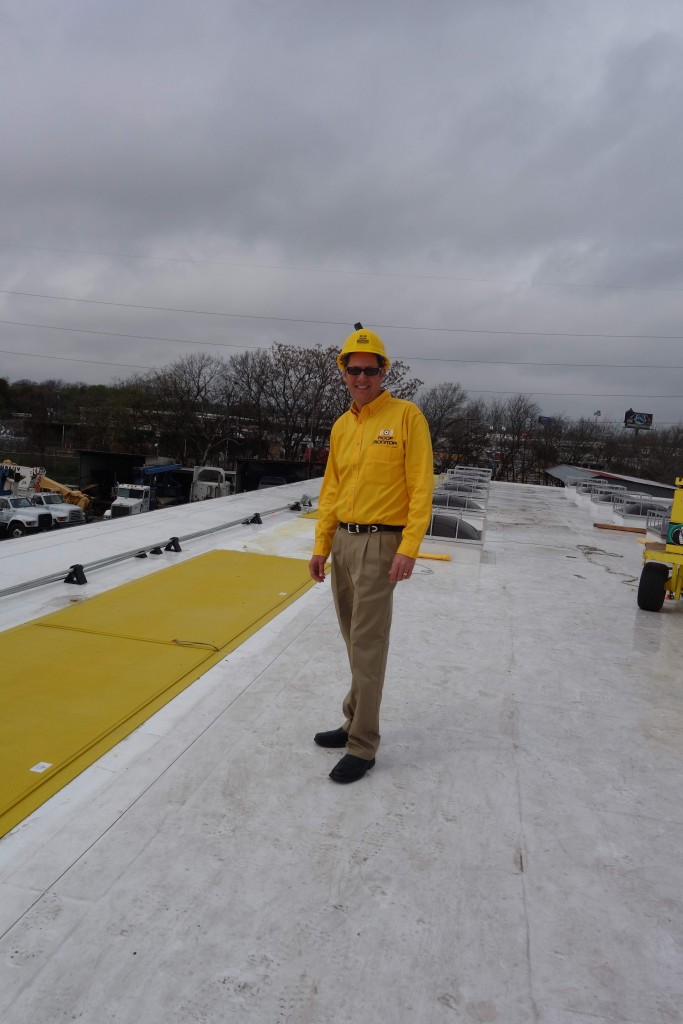 Roof Monitor CEO Brad Beldon shows how the bright yellow Edge Defense™ safety system is installed upon a commercial rooftop.